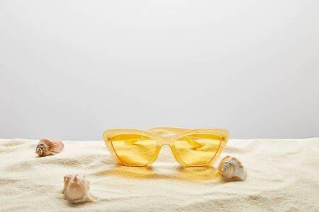 Yellow stylish sunglasses on sand with seashells on grey background