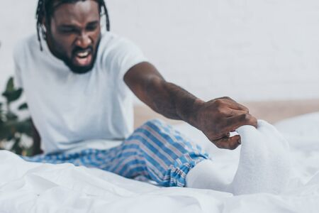 Selective focus of screaming African American man suffering from foot pain in bedroom Stockfoto