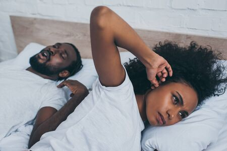 Selective focus of African American woman plugging ear with finger while lying near snoring husband Archivio Fotografico - 125527751