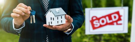 Panoramic shot of realtor holding carton house model and keys near board with sold letters Фото со стока