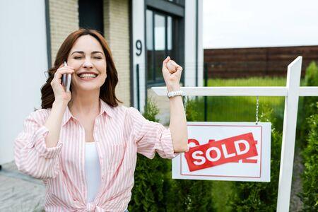 Fröhliche Frau mit geschlossenen Augen, die beim Telefonieren auf dem Smartphone gestikuliert Standard-Bild