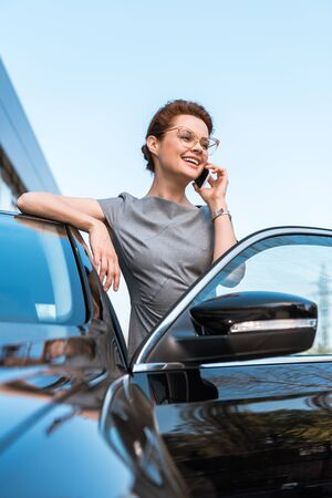 Low angle view of happy woman talking on smartphone near black car