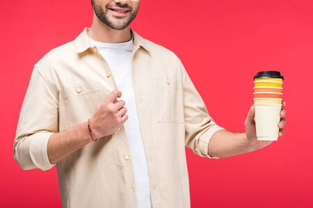 Cropped view of man holding paper cups with coffee to go isolated on pink background