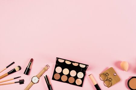 Top view of wristwatch, earrings and decorative cosmetics on pink background