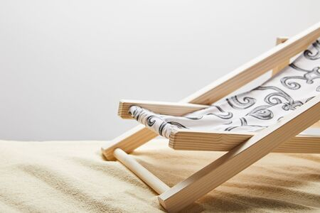 Wooden deck chair on sand on grey background with copy space