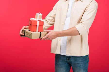 Cropped view of man holding presents on pink background