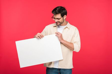 Smiling handsome man holding empty board isolated on pink background
