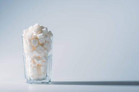 Glass full of white refined sugar cubes on grey background with copy space Imagens