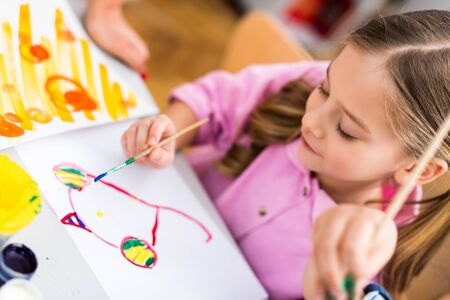 Selective focus of cute kid painting on paper with paintbrush