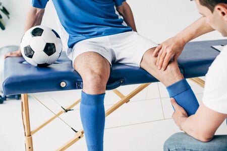 Vista parcial del fisioterapeuta masajeando la pierna del jugador de fútbol en el hospital Foto de archivo