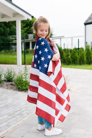 Cheerful kid smiling while standing with American flag near house