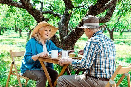 Cheerful senior woman in straw hat looking at husband near tree