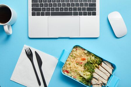 Top view of digital devices, cup of coffee and lunch box with tasty chicken, rice and broccoli on blue background, illustrative editorial