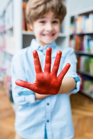 Selective focus of happy kid showing painted hand with red gouache paint