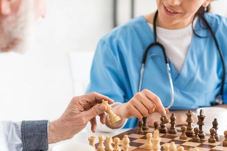 Cropped view of nurse and senior man sitting on kitchen, and playing in chess