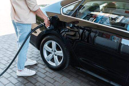 Cropped view of man holding fuel nozzle and refueling car with benzine at gas station Stock Photo