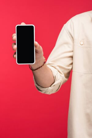 Partial view of man holding smartphone with blank screen isolated on pink background