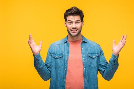 Confused handsome man gesturing with hands and looking at camera isolated on yellow background