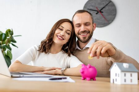 Selective focus of happy man putting golden coin in pink piggy bank near attractive woman