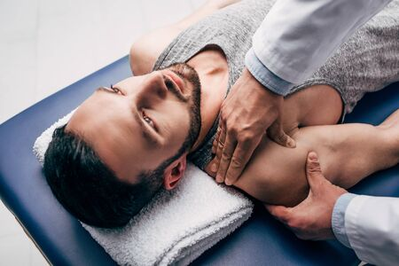 Chiropractor massaging shoulder of man on Massage Table in hospital