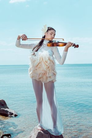 Adult woman in white swan costume with violin playing music on blue river background