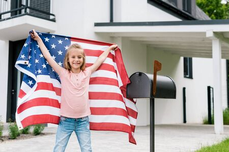 Happy kid standing and holding American flag near mail box and house