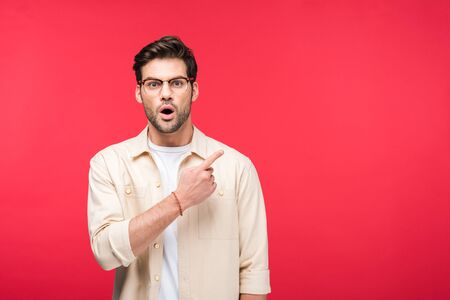 Surprised handsome man pointing with finger isolated on pink background with copy space Banco de Imagens