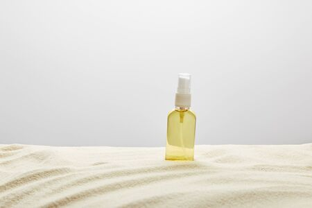 Suntan oil in transparent yellow spray bottle in sand on grey background