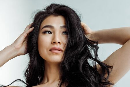 Low angle view of attractive brunette Asian woman touching hair on grey background