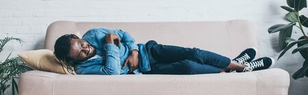 Panoramic shot of African American man suffering from abdominal pain while lying on sofa