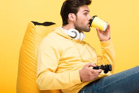 Man drinking coffee to go on bean bag chair and playing Video Game isolated on yellow background Stock Photo