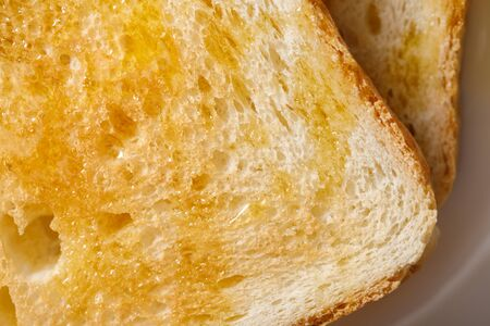 Close up view of toasts with honey on white plate