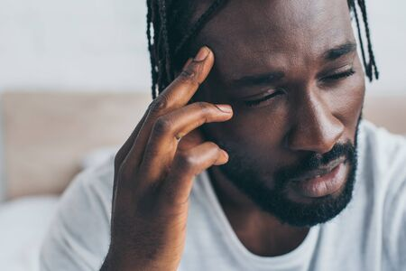 Exhausted African American man suffering from headache in bedroom
