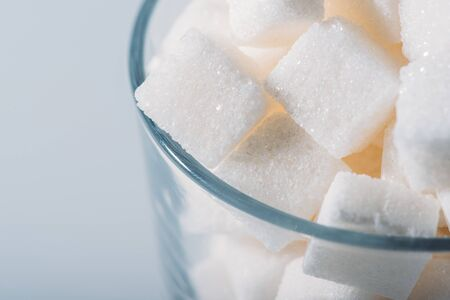 Close up view of white sugar cubes in glass on grey background Imagens - 125528297