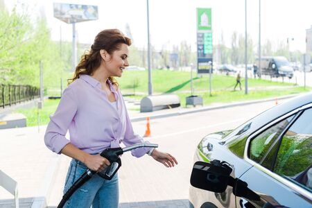 Cheerful woman holding fuel pump near black car at gas station