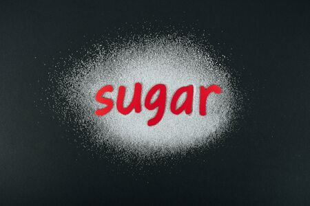 Top view of white sugar crystals with red paper cut word sugar on black background