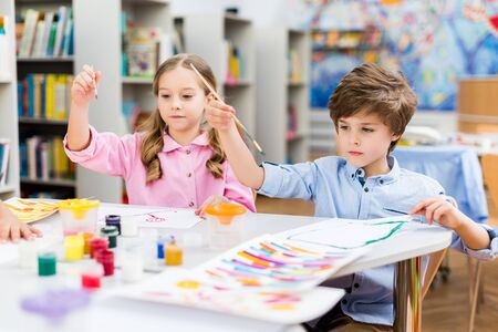 Cute kids holding paintbrushes colorful gouache jars and papers 写真素材
