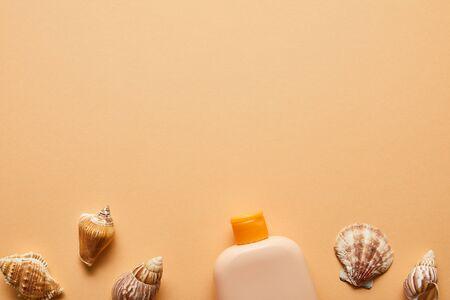 Top view of sunscreen lotion in bottle near seashells on beige background