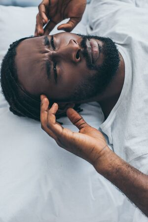 Unhappy African man suffering from headache while lying in bed