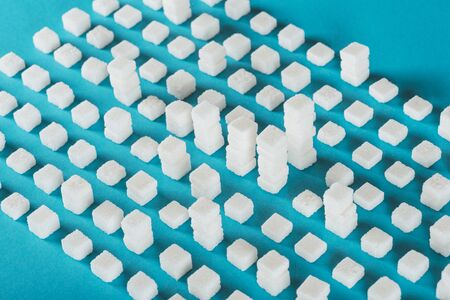 White sugar cubes arranged in rows and stacks on blue surface background 스톡 콘텐츠