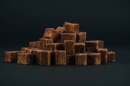 Pile of unrefined brown sugar cubes on black background