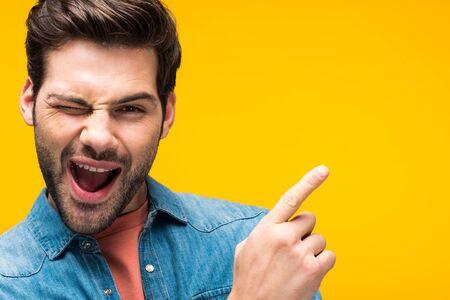 Hombre guapo apuntando con el dedo y guiñando un ojo aislado sobre fondo amarillo Foto de archivo