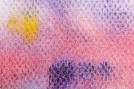Close up view of yellow and purple watercolor paint spills on textured background