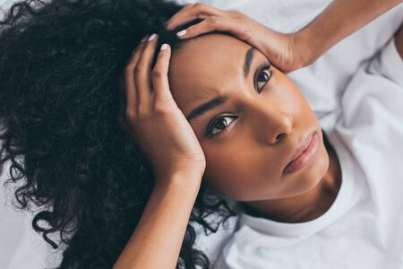 Beautiful African American woman looking up while suffering from headache