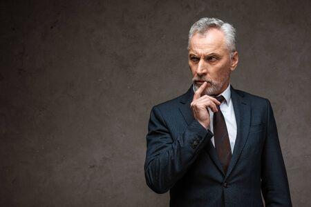 Homme d'affaires barbu pensif en costume touchant le visage sur fond gris