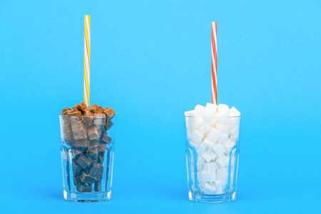 Glasses with straws and white and brown sugar cubes on blue background