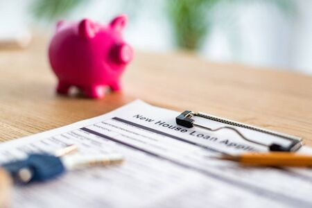 Selective focus of clipboard with new house loan lettering on document near pencil, keys and pink piggy bank Stok Fotoğraf