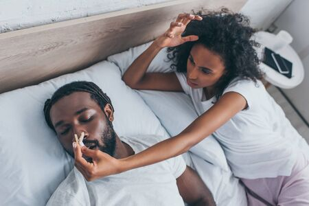 Young African American woman pinning nose of snoring husband