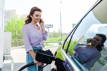 Happy woman holding fuel pump while refueling car with benzine and talking on smartphone