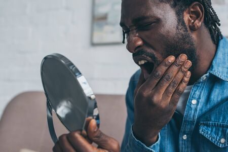 Upset African American man looking at mirror while suffering from tooth pain Stockfoto
